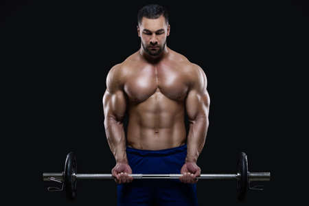 Handsome fitness man is standing with a heavy barbell ready to workout isolated on black background 版權商用圖片