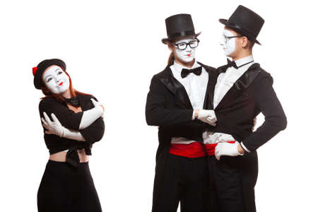 Portrait of three mime artists performing, isolated on white background. Two men embrace, and the girl is perplexed. Symbol of tolerance, same-sex marriage, the LGBT community Imagens