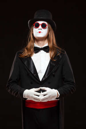 Portrait of male mime artist performing, isolated on black background. Man is standing straight putting his hands in the lock