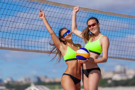 Two beautiful girls in bright swimsuits congratulate each other on winning a beach volleyball match