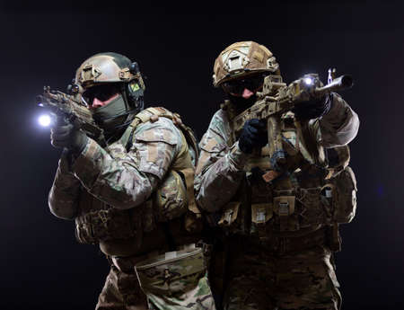 Two soldiers in military gear and bulletproof vests cover each other and raise their submachine guns to their faces taking aim, in full combat readiness, isolated on black background