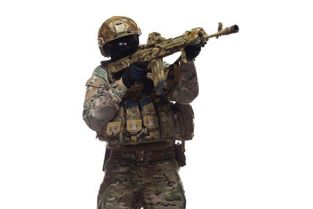 Side view of army man dressed in camouflage and full military equipment, wearing helmet, glasses and balaclava, holding machine gun, taking aim and preparing to shoot, isolated on white background