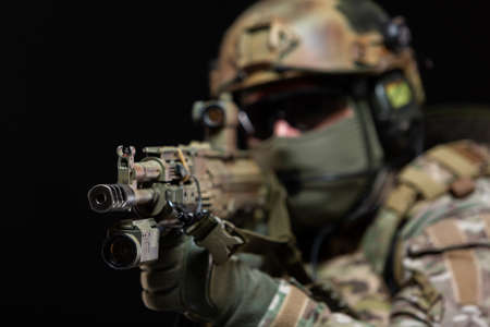 Close up of a soldier in camouflage and full military gear, wearing a helmet, glasses and protective mask, raises a rifle to his face and taking aim, preparing to shoot, isolated on black background Banque d'images