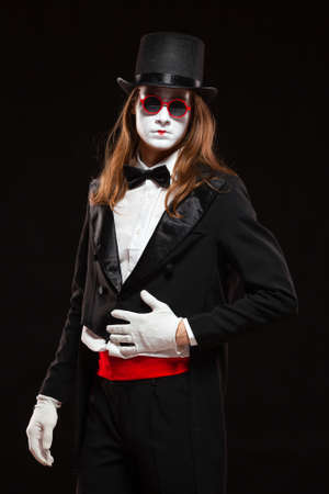 Portrait of male mime artist performing, isolated on black background. Man is standing straight with his hand on the stomach