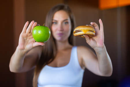 Young attractive girl is making choice between healthy and harmful food holding a green apple and a burger in her hands. Concept of proper nutrition, healthy food, fast food