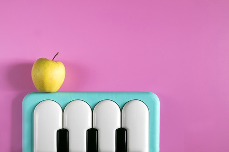 Baby blue piano music keyboard toy and yellow apple on the pink background. Minimal style concept. Punchy Pastels. Top view