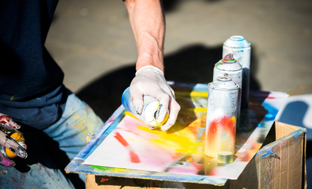 Artist Holding a Spray Paint And Drawing on Paper