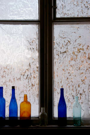Window covered in rime. There are some coloured bottles on the sill. Stock Photo - 8796094