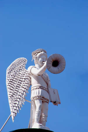 white angel with trumpet and book in hands photo