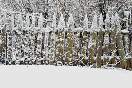 Snow draws ornaments on old farmhouse fence photo