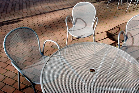 Silvery metal table and three chairs in the morning light