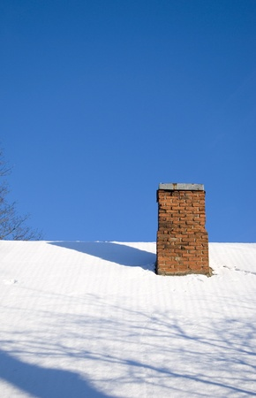 Snowy roof and red brick chimney in background of blue sky Stock Photo
