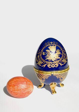 Orange Easter egg near copy of Faberge egg isolated on a white background Stock Photo - 9087862