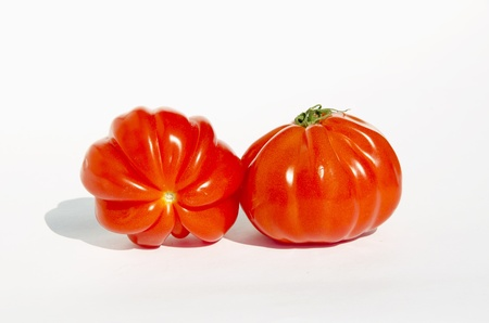 intresting: Two intresting red tomatoes with shadows on a white background. Ecological and healthy begetables.
