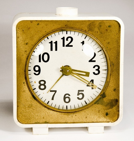 Ancient clock with three arrows showing 3:20. Old white gold alarm clock. photo