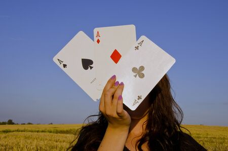 anonym: Young woman,holding cards in front of her face. Three of a kind.