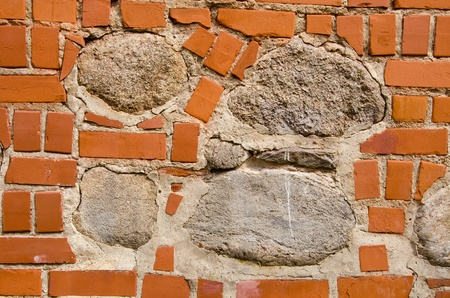 intresting: Intresting old wall fragmentmade of red bricks and stones. Architectural background. Stock Photo