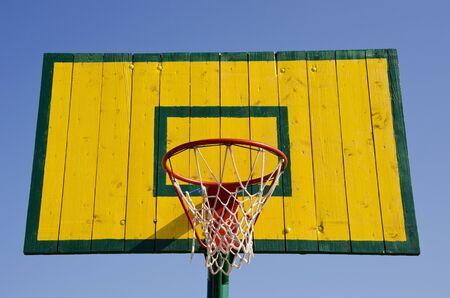 basketball net: Basketball board painted green and yellow with net on the hoop.