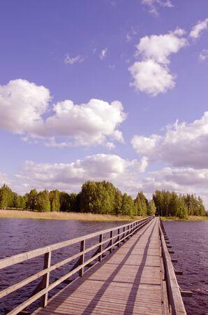 Longue passerelle en bois avec garde-corps sur le lac et l'homme marche au loin. Des for�ts dans la distance et le ciel nuageux. Banque d'images - 10643027