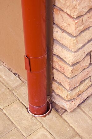 eau de pluie: Red descente d'eau pluviale en �tain sur le coin maison faite de briques d�coratives.