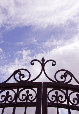 Sky view through old decorated metal gates. Architectural solution made ??of steel. photo