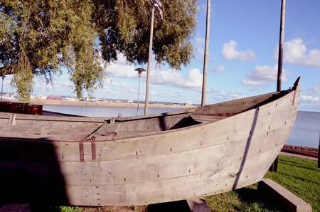 Antique wooden boat in exhibition on the lake shore. Stock Photo