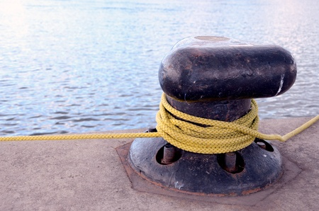 Thick rope rotated around mooring pole berth.