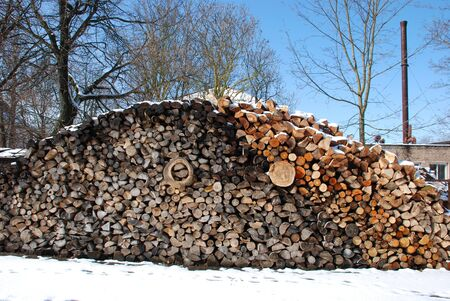 boiler house: Snow covered firewood pile next to boiler house. Preparing for the cold season.