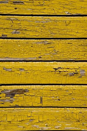 Ancient yellow painted wooden wall with peeling paint background. photo