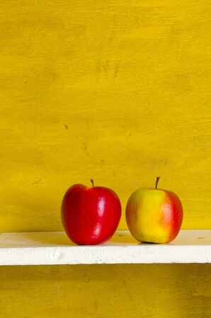 shelve: Apples on white shelve yellow wall background. Healthy ecologic fruit food.