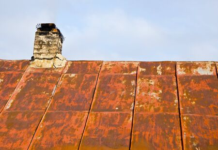 Roof made of rusty tin and ramshackle brick chimney of an old abandoned country house. photo