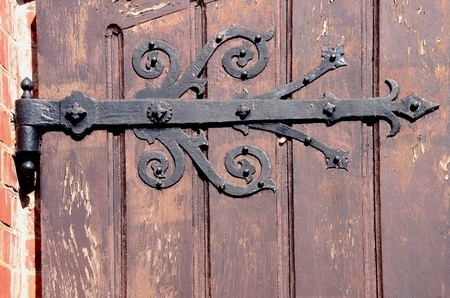 Detail of old decorative hinges holding wooden door. Architectural backdrop fragment. photo