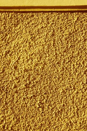 Yellow-painted textured walls macro closeup. Architectural background details.