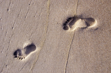Bare human footprints in the sand sea. Rest near sea.