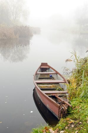 Wooden rowing boat stands on coast of river sunken in dense fog.
