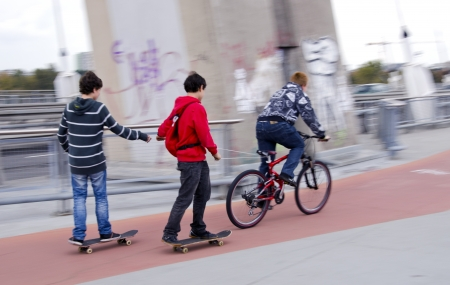 Teenagers riding bikes and skateboards on urban bicycle trail.