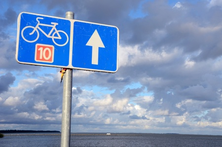 Bicycle path sign number ten 10 near lake and cloudy blue sky. photo
