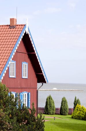 Rural living house near sea and green yard with thujas. Interesting architecture building. photo