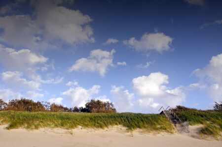 Coastal dunes and stairs leading up covered with sea sand. Blue sky with clouds.  photo