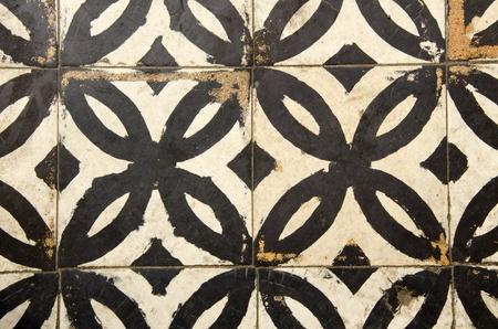 Antique floor tiles abraded backdrop in corridor.