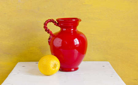 Still life. Red vase and yellow lemon on a shelf.