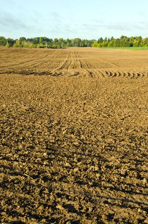 Plow of agricultural fields in autumn. Background of dirty earth ground. photo