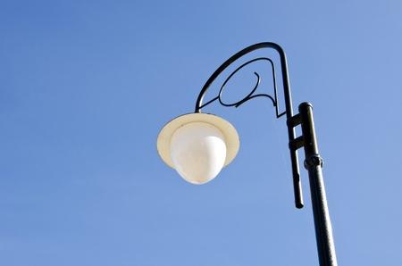Glass ball lamp on metal decorative pole. Park lighting.  photo