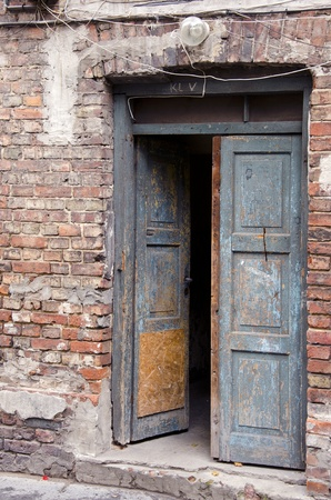 Ancient grunge masonry house wooden doors and red brick wall background.  Stock Photo - 12567457