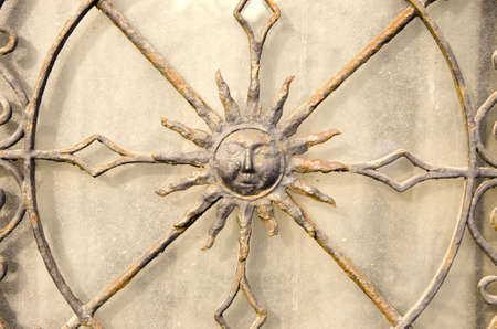Closeup of decorative metal gate. Sun is shown in middle. Stock Photo - 12567460
