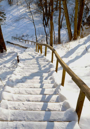 Oak stairs and handrail on  steep mountain slope covered with snow in winter.  photo