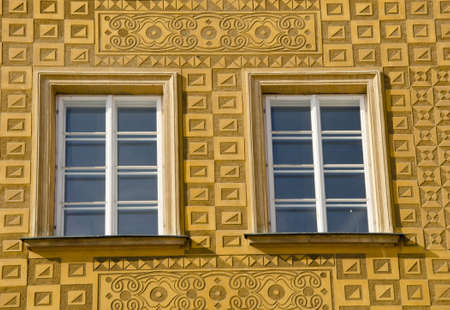 ornamented: Ancient building architectural decorative windows ornamented yellow wall.