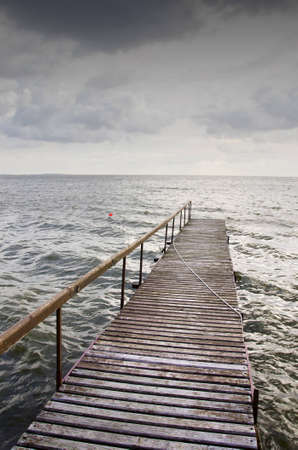 Wooden bridge on wavy lake. Red buoy in the water. Cloudy sky before storm.  Stock Photo