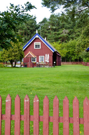 Wooden colorful house in rural homestead. Well. Fence. Green lawn yard.