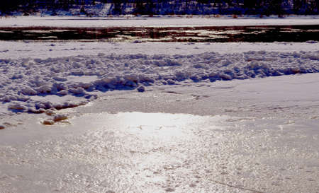Partially frozen but still flowing river, and floe carried by water  Natural sun reflections   photo